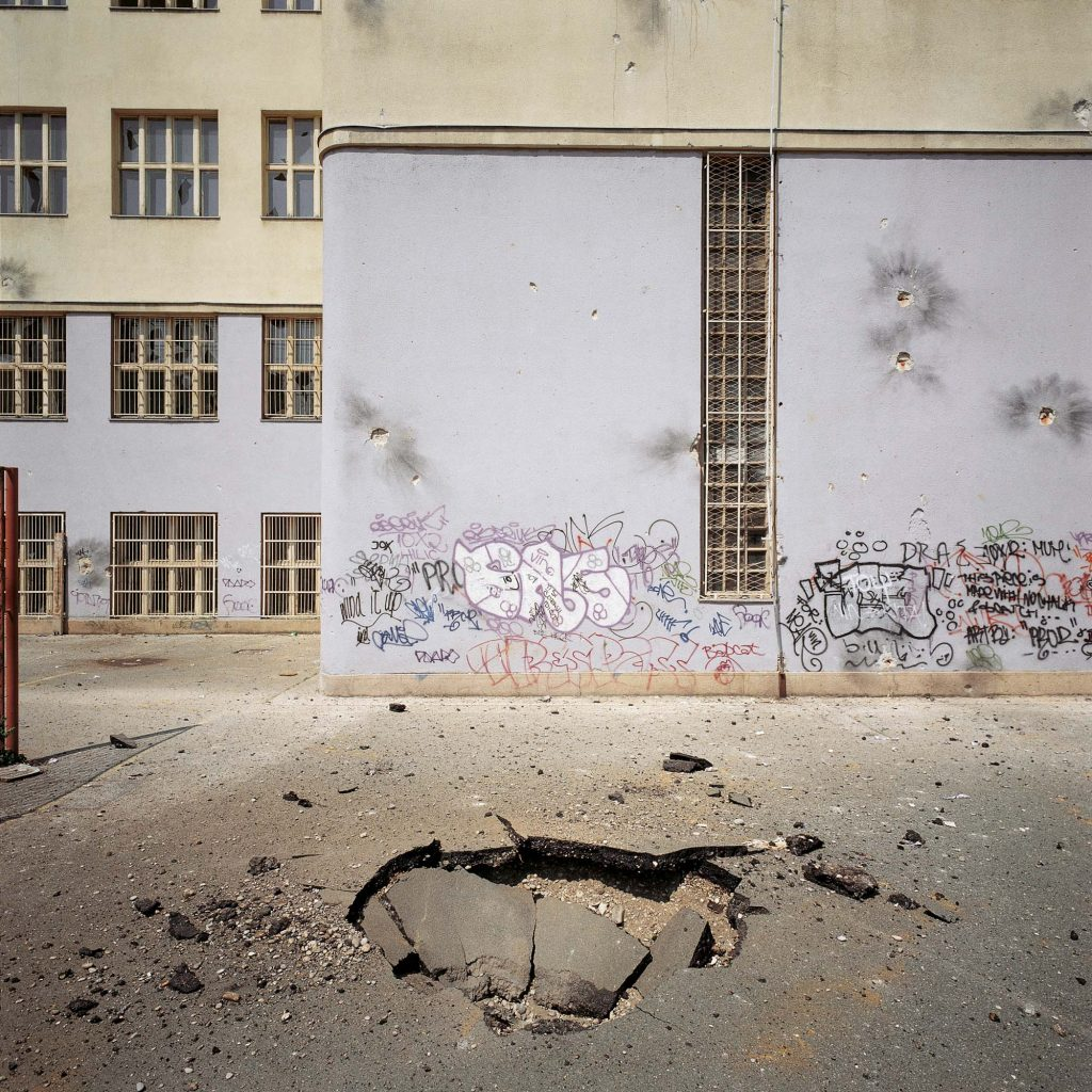 THE SCHOOLYARD OF THE SECONDARY SCHOOL IN THE KRIŽANIĆEVA STREET, ZAGREB, MAY 1995 A hole in the ground as a result of the missile attack