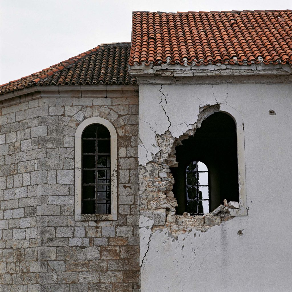 ST. JOHN THE BAPTIST'S CHURCH, THE VILLAGE OF KONJEVRATE, NEAR ŠIBENIK, FEBRUARY 1992 A hole made by a deliberate tank shell hit from close vicinity