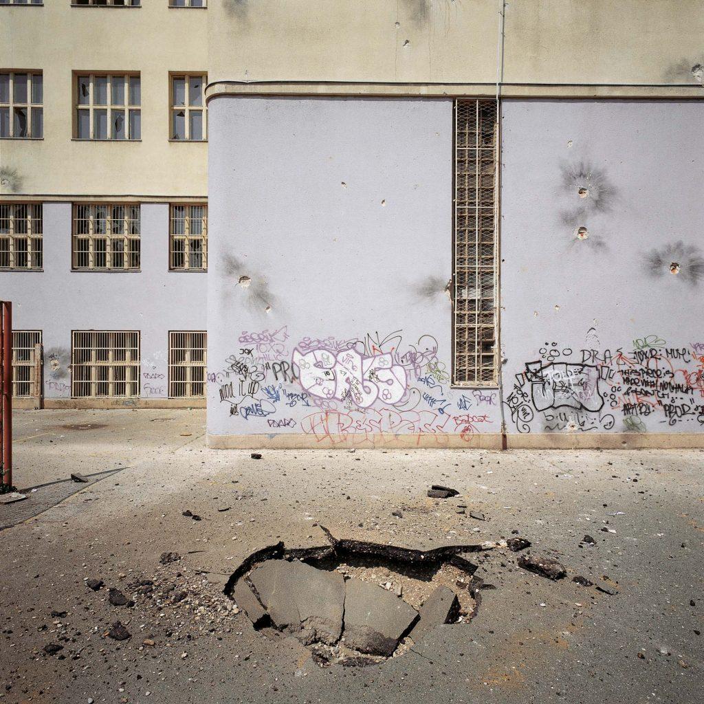 DVORIŠTE GIMNAZIJE U KRIŽANIĆEVOJ ULICI, ZAGREB, SVIBANJ 1995. Rupa nastala na školskom igralištu prigodom raketnog napada
