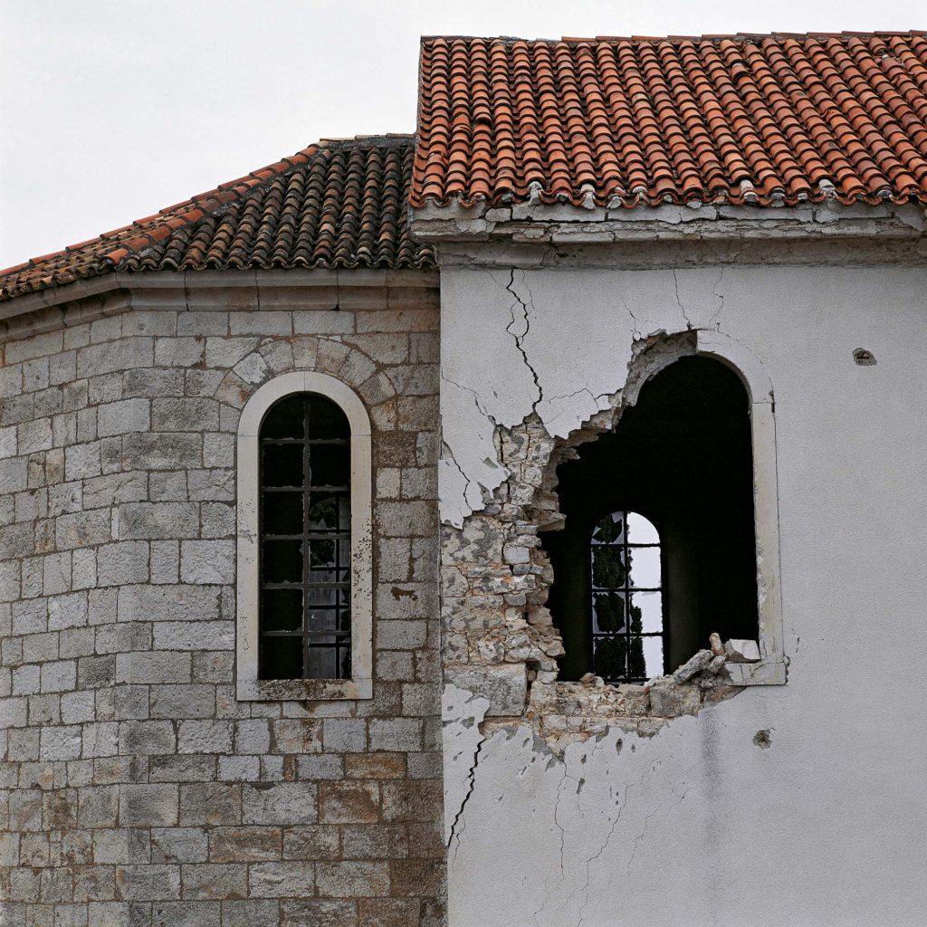 CRKVA SV. IVANA KRSTITELJA, SELO KONJEVRATE KOD ŠIBENIKA, VELJAČA 1992. Rupa od namjernoga pogotka tenkovskom granatom iz neposredne blizine